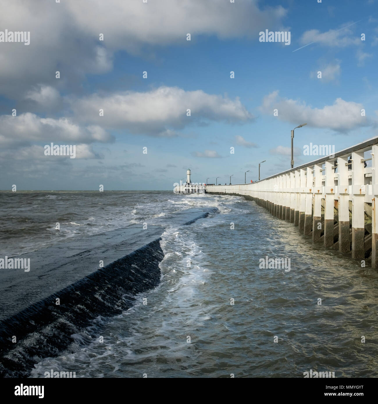 View on waves and old wooden pier of Nieuwpoort in Belgium. Stock Photo