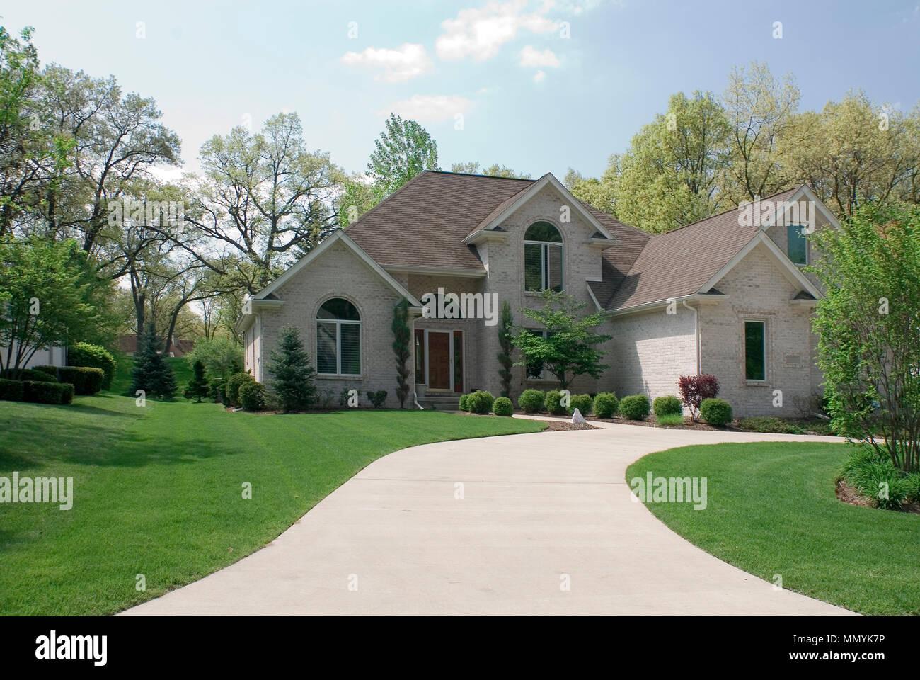 Beautiful Beige Brick Home Featuring A Complex Roof Design