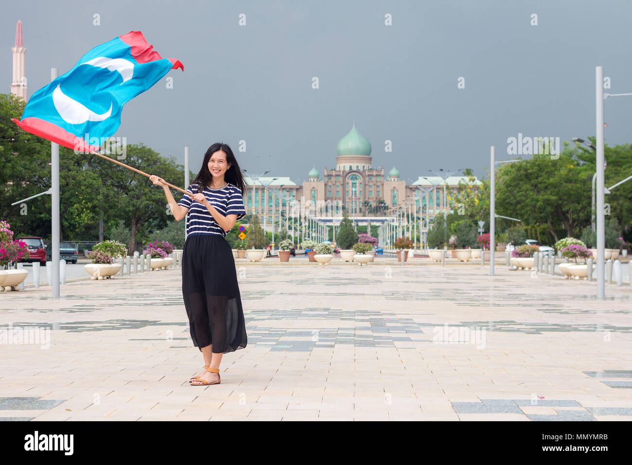 PUTRAJAYA MALAYSIA - 13 May 2018 - a female PKR (Parti Keadilan) supporter happily waving the flag of wining party in front of the government administ - Stock Image