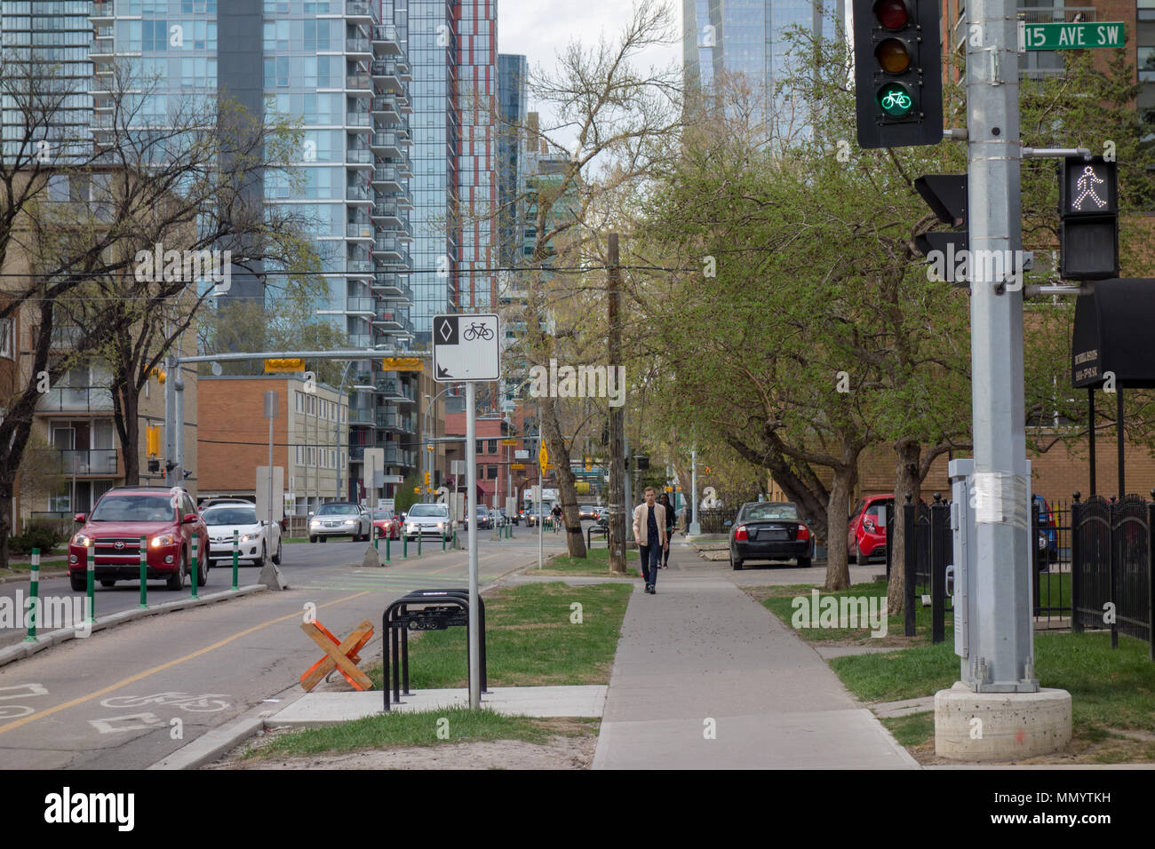 Pedestrian and bike signals next to dedicated bike lane along 5th Street SW in Calgary, Alberta. - Stock Image