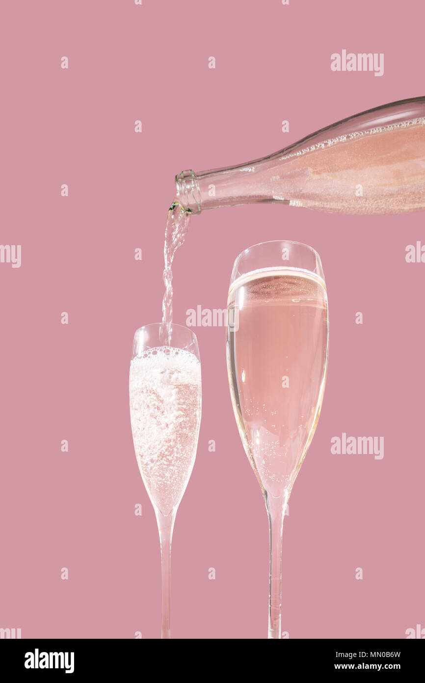 Valdobbiadene Prosecco flutes and a bottle, pink background, in pop contemporary style. Prosecco Superiore is an italian sparkling wine - Stock Image