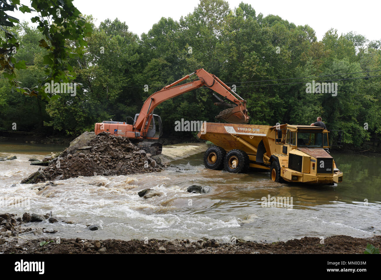 An excavator loads a dump truck with concrete, rock and soil from Roaring River Dam in Jackson County, Tennessee Aug. 1, 2017. The Tennessee Wildlife Resources Agency is removing the dam, built in 1976 by the U.S. Army Corps of Engineers Nashville District.  The dam in Jackson County, Tennessee was at risk of failure and the Corps of Engineers determined that it would be better to remove the dam as it was no longer needed as a fish barrier on the Cumberland River tributary.  Partners in the joint effort to remove the dam include TWRA, Corps of Engineers, The Nature Conservancy, U.S. Fish and W - Stock Image