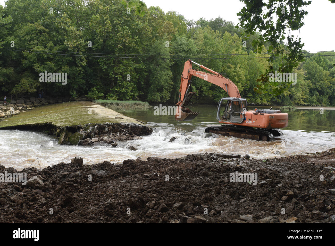 An excavator moves into position to remove Roaring River Dam in Jackson County, Tennessee Aug. 1, 2017. The Tennessee Wildlife Resources Agency is removing the dam, built in 1976 by the U.S. Army Corps of Engineers Nashville District.  The dam in Jackson County, Tennessee was at risk of failure and the Corps of Engineers determined that it would be better to remove the dam as it was no longer needed as a fish barrier on the Cumberland River tributary.  Partners in the joint effort to remove the dam include TWRA, Corps of Engineers, The Nature Conservancy, U.S. Fish and Wildlife Service, Tennes - Stock Image