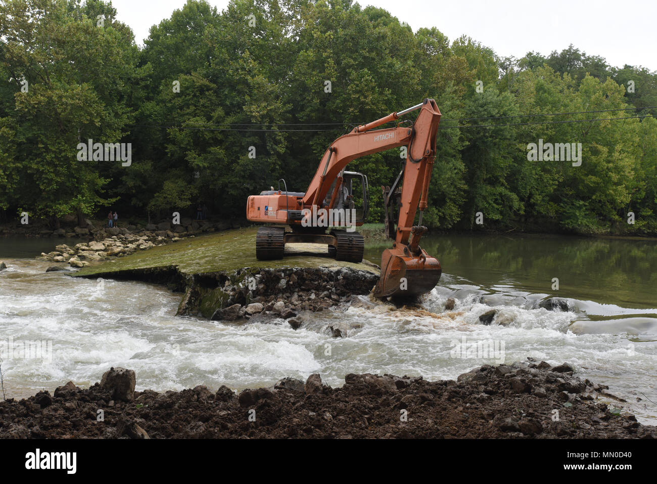 An excavator removes the concrete cap from Roaring River Dam in Jackson County, Tennessee Aug. 1, 2017. The Tennessee Wildlife Resources Agency is removing the dam, built in 1976 by the U.S. Army Corps of Engineers Nashville District.  The dam in Jackson County, Tennessee was at risk of failure and the Corps of Engineers determined that it would be better to remove the dam as it was no longer needed as a fish barrier on the Cumberland River tributary.  Partners in the joint effort to remove the dam include TWRA, Corps of Engineers, The Nature Conservancy, U.S. Fish and Wildlife Service, Tennes - Stock Image