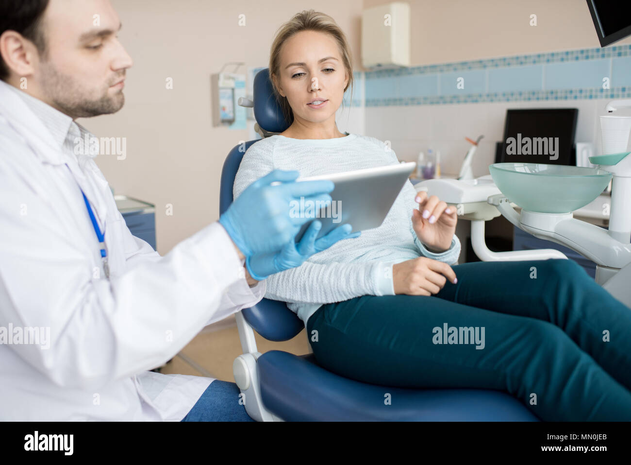 Man in white apparel showing tablet to young client sitting in chair in dentist cabinet. - Stock Image