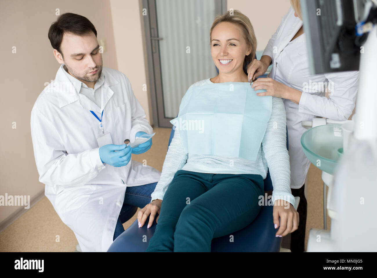 Crop assistant preparing cheerful girl while dentist getting special clean tools from bag. - Stock Image