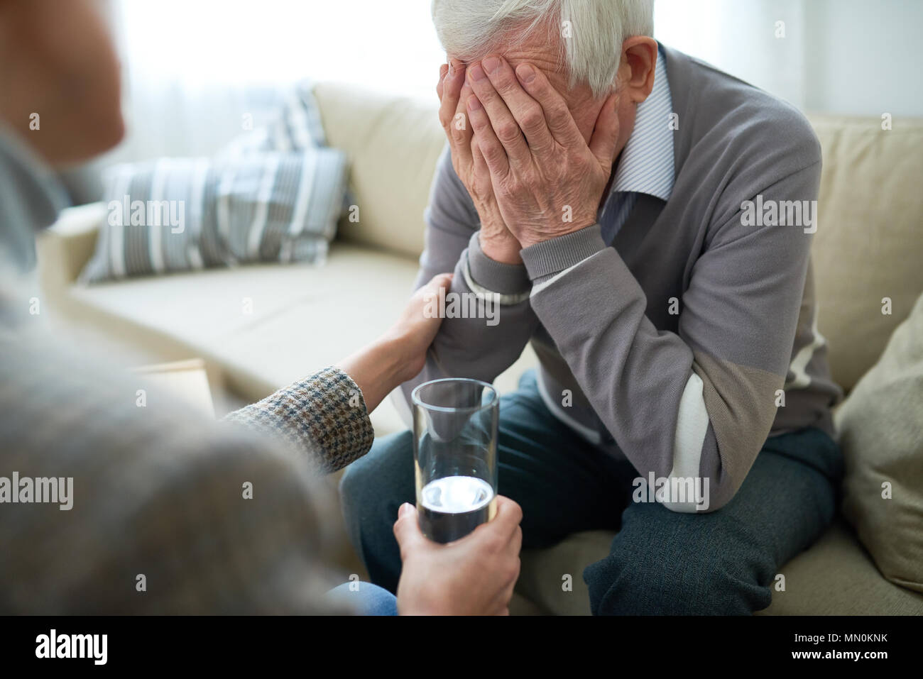 Crop compassionate person consoling elderly man in assisted living home holding glass of water. Stock Photo