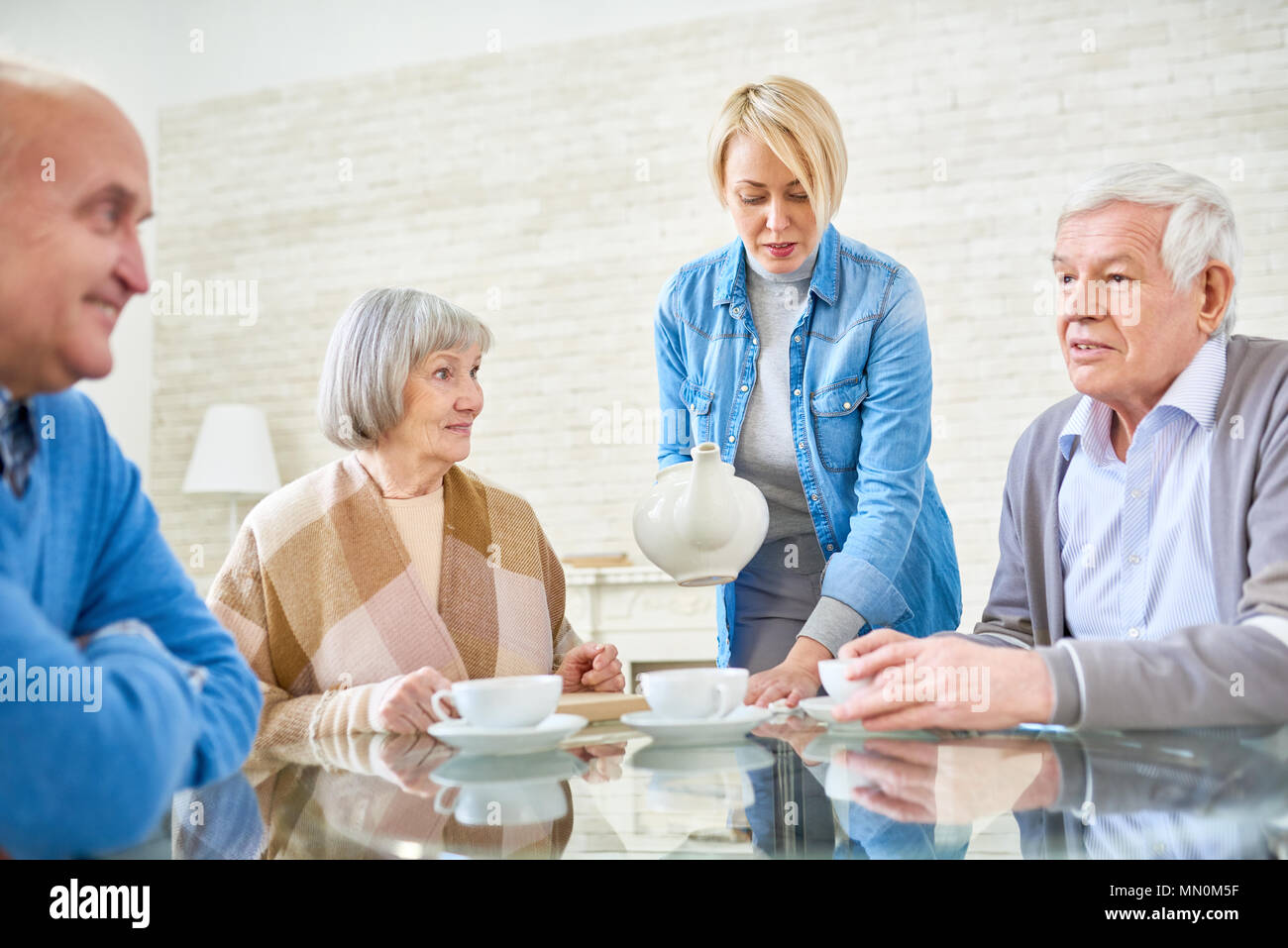 Woman pouring tea for senior patients in assisted living home sitting at table and chatting. - Stock Image