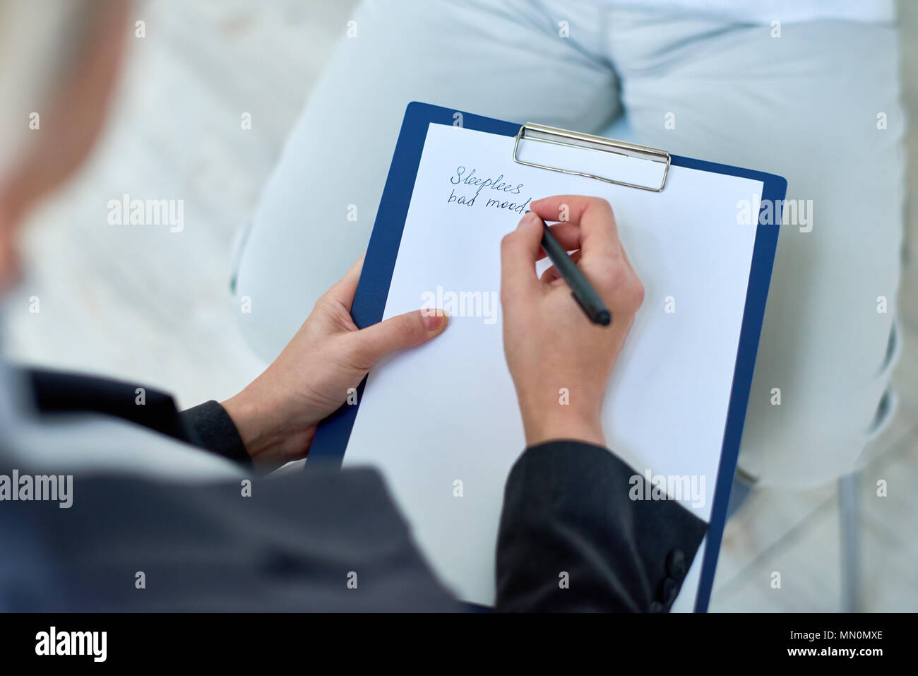 Crop shot from above of doctor taking notes of senior patient complaints working in assisted living home. - Stock Image