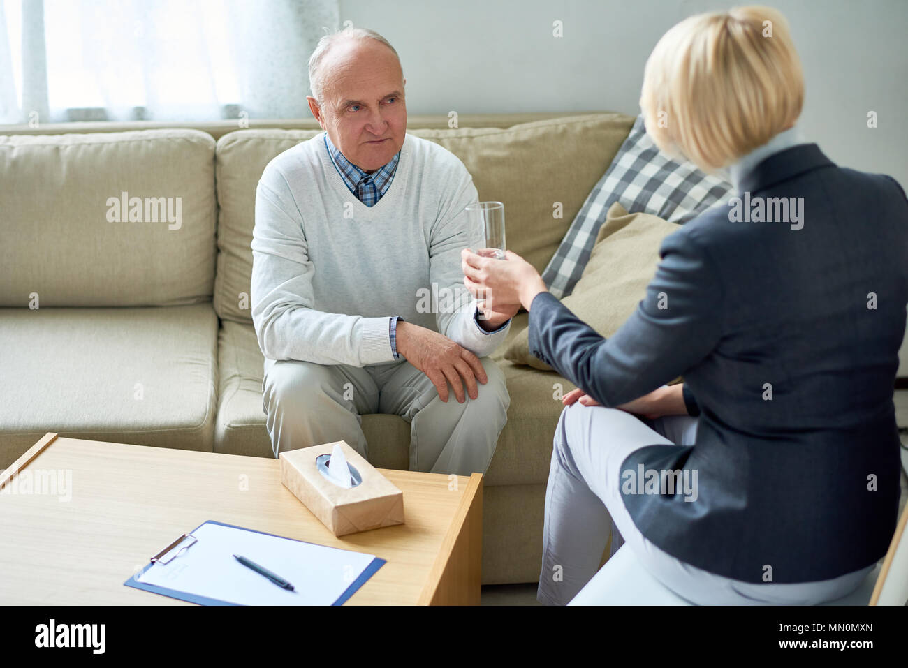 Anonymous therapist giving glass of water to elderly man having consultation in assisted living home. - Stock Image