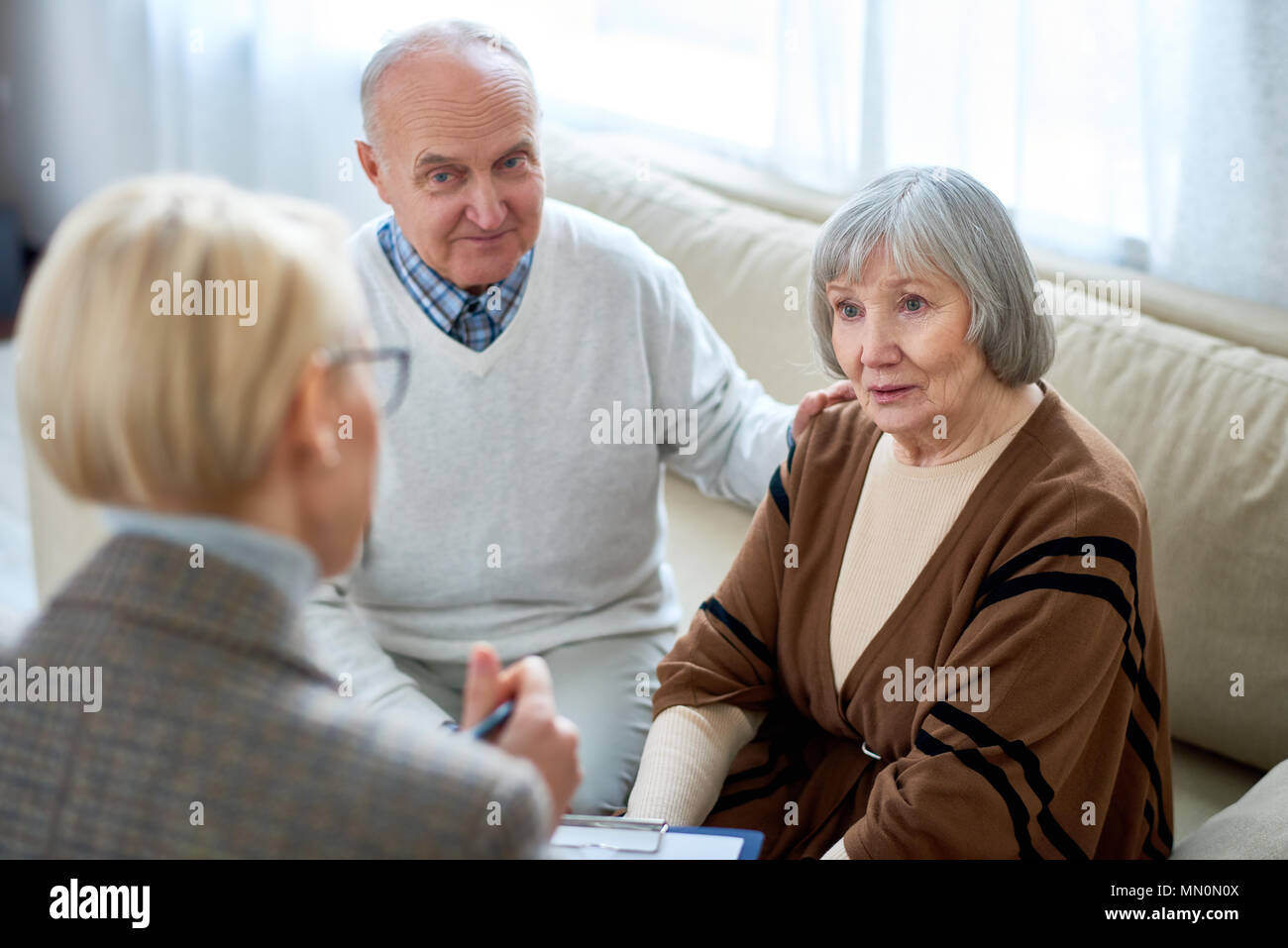 Anonymous therapist having meeting with elderly patients in nursing home giving consultation. - Stock Image