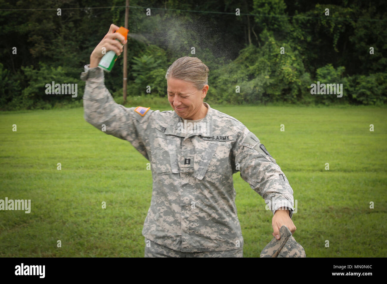 Army Reserve Soldier Capt. Jennifer Dennis, G-1 personnel management branch chief, 335th Signal Command (Theater) sprays herself with bug spray to avoid ticks and any other insects in the New Jersey forests during a land navigation exercise on Joint Base Mcguire-Dix-Lakehurst, New Jersey, Aug. 8. More than 100 Army Reserve Soldiers from the 335th SC (T) Headquarters in East Point, Georgia are at the base conducting a variety of training exercises as part of the unit's annual training. (Official U.S Army Reserve photo by Spc. Matthew E. Drawdy) - Stock Image