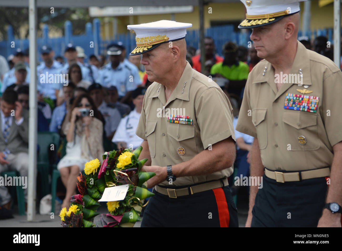 Gen. Robert B. Neller (left), Commandant of the Marine Corps, carries a wreath to be laid at the Solomon Scouts and Coastwatchers Memorial during 75th Anniversary of the Battle for Guadalcanal ceremonies at Honiara, Guadalcanal in the Solomon Islands, on Aug. 7, 2017. Solomon Scouts and Coastwatchers provided invaluable support and aid to the Allied effort during World War II. Two Solomon Islanders, Eroni Kumana and Biukuk Gasa, rescued U.S. Navy Lt. John F. Kennedy and his 10 surviving crew fro PT-109, August 1943. Kennedy later became president of the United States. (U.S. Army photo by Staff - Stock Image