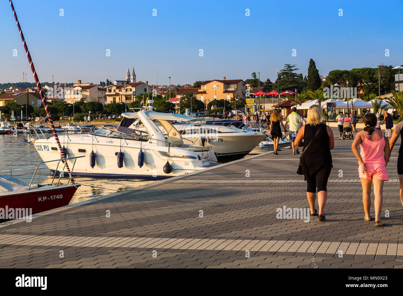 MEDULIN, CROATIA - JUNE 24, 2017. People enjoy the beautiful Medulin downtown waterfront with boat marinas - Stock Image