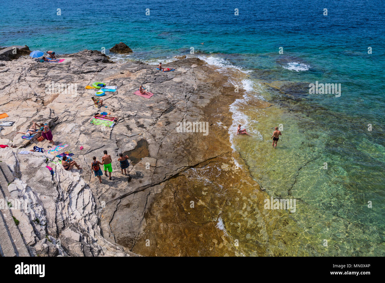People on a rocky beach in Pula, Punta Verudela, Croatia - Stock Image