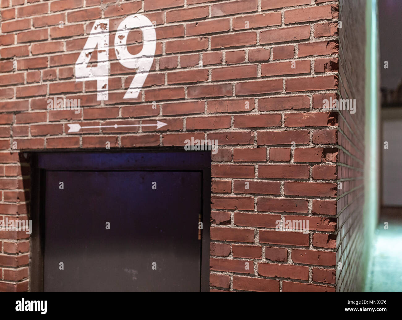 number 49 painted on a brick wall with a painted white arrow point down the side of the industrial building above a black door - Stock Image