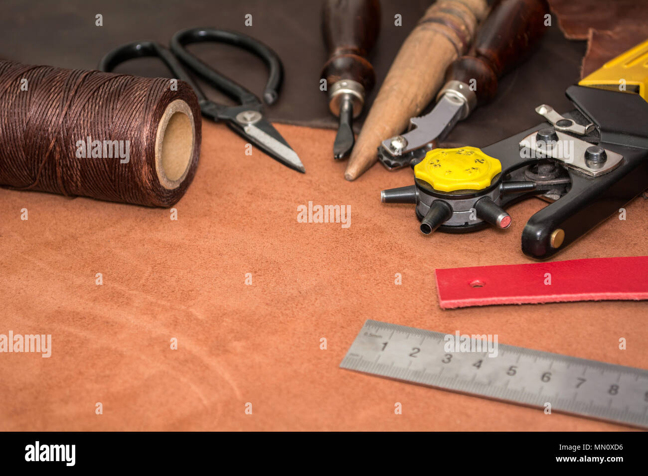 Tools for crafting and pieces of brown leather. Manufacture of leather goods. - Stock Image