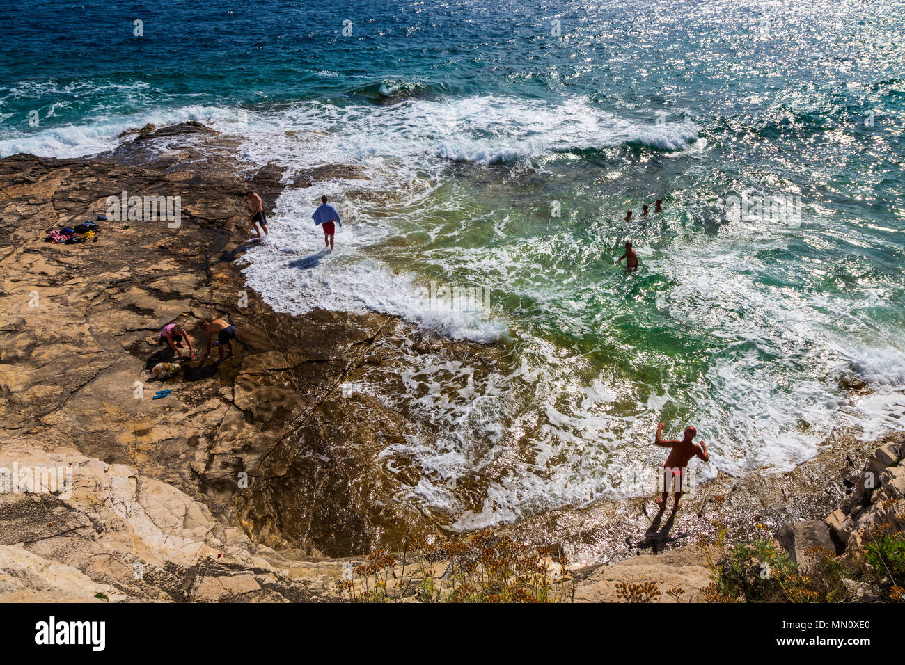 People on a rocky beach in Pula, Croatia - Stock Image