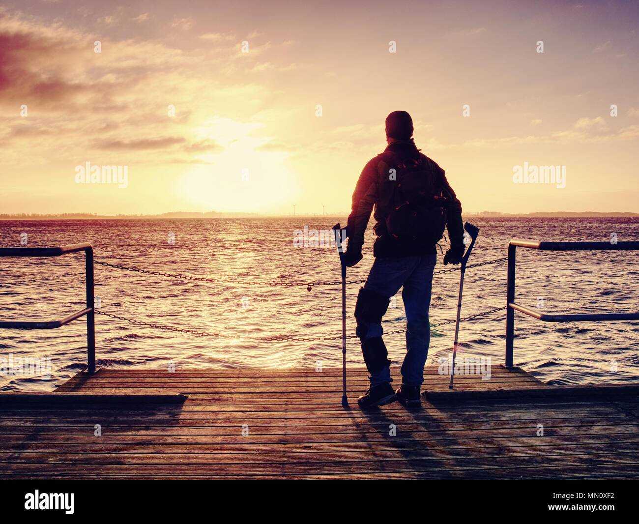 Hurt man with hooded jacket and forearm crutches  looking sadly into sea water. Traveler  stand on sea bridge within  morning and thinking. Nostalgic  - Stock Image