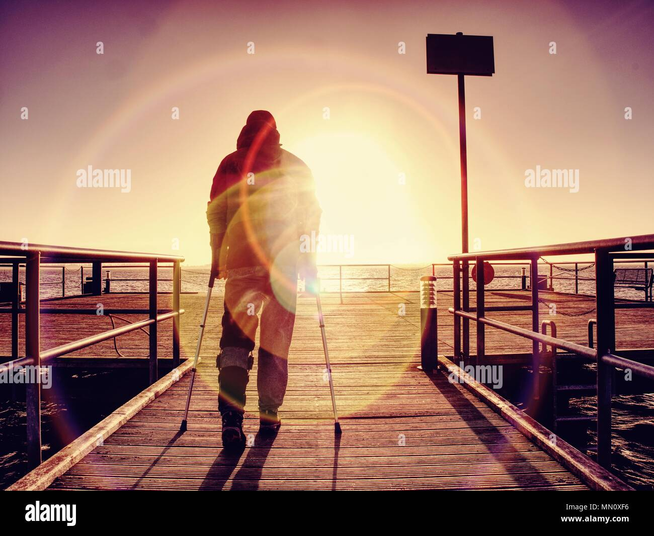 Hurt man with hooded jacket and forearm crutches  standing on sea bridge within  early morning and thinking. Gloomy nostalgic silhouette of sad lonely - Stock Image