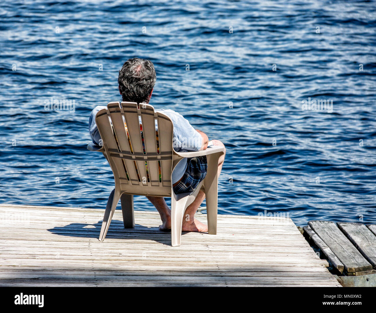 A relaxing, restful sun-lit image from behind of a man lounging in a chair at the end of a small wooden dock in front of the clearest blue lake. - Stock Image