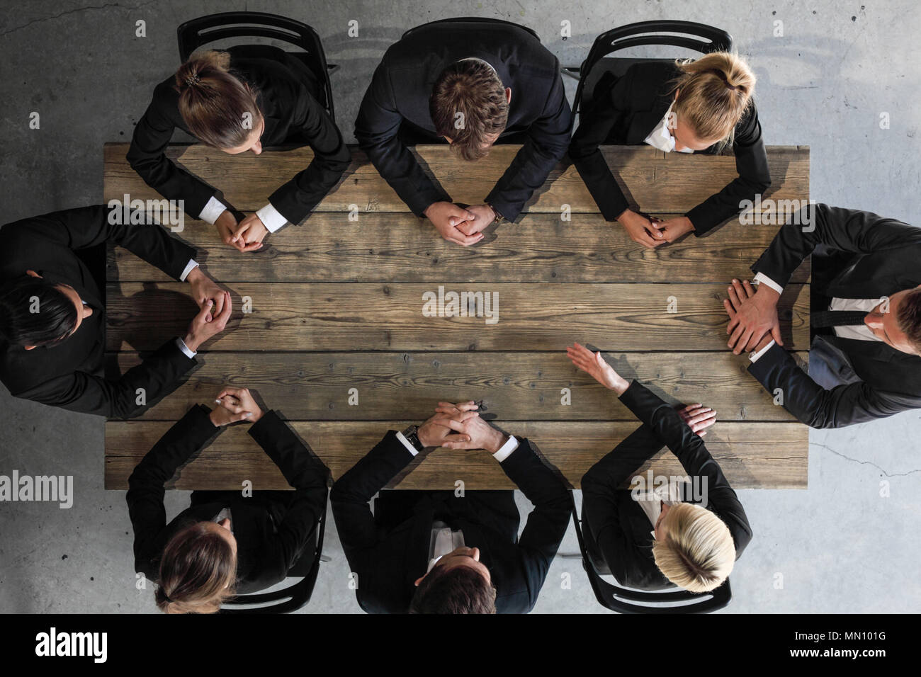 Business meeting concept, people in formal wear sitting around wooden table - Stock Image