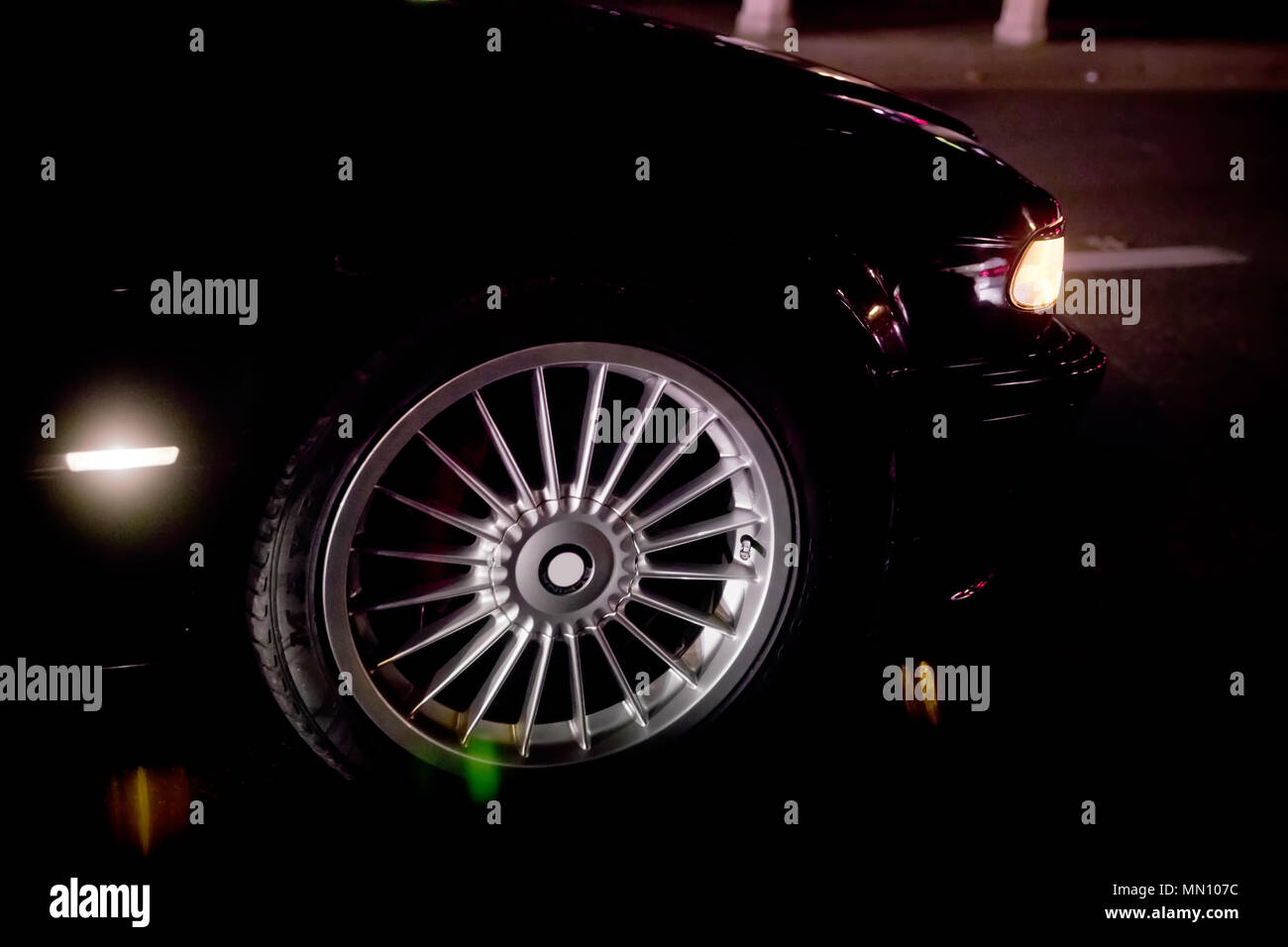 A car burnout at a drag racing track. Car tire Night on the way. Car tires in automobile . luxury car wheel close-up . fuel efficient car tires on black background. - Stock Image