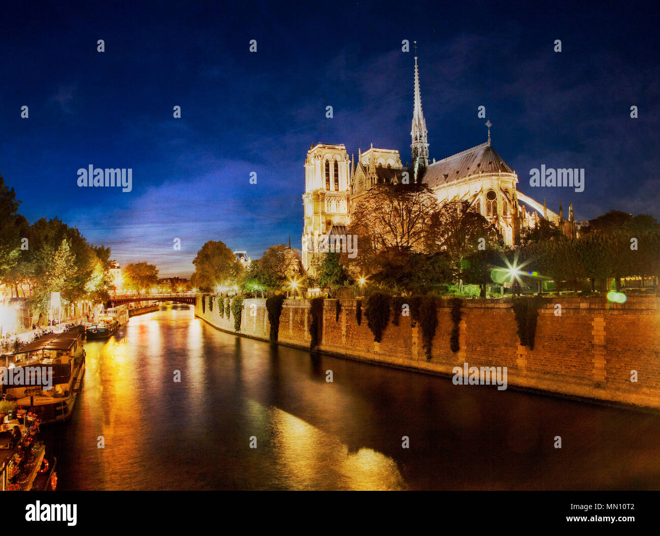 Nighttime comes over Notre Dame along the River Seine.  Paris, France. - Stock Image