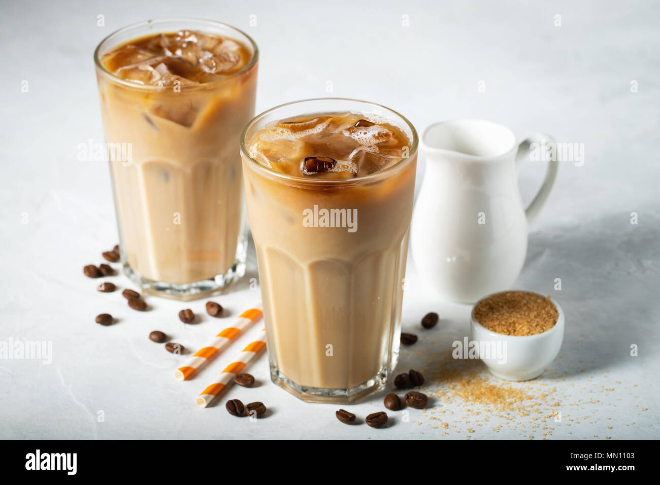 Ice coffee in a tall glass with cream poured over and coffee beans. Cold summer drink on a light blue background - Stock Image