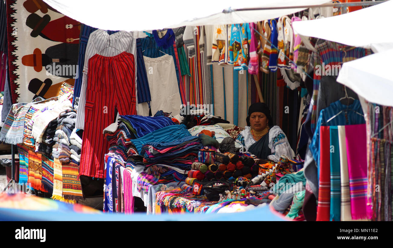 Indigenous woman sitting selling her weavings and crafts in the Plaza de los Ponchos - Stock Image