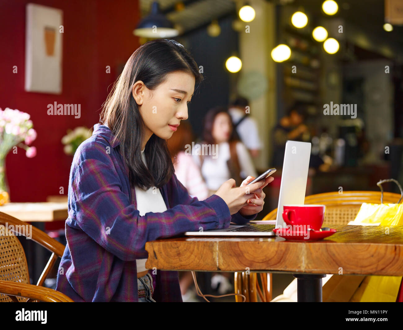young asian woman sitting in coffee shop using mobile phone and laptop  computer.