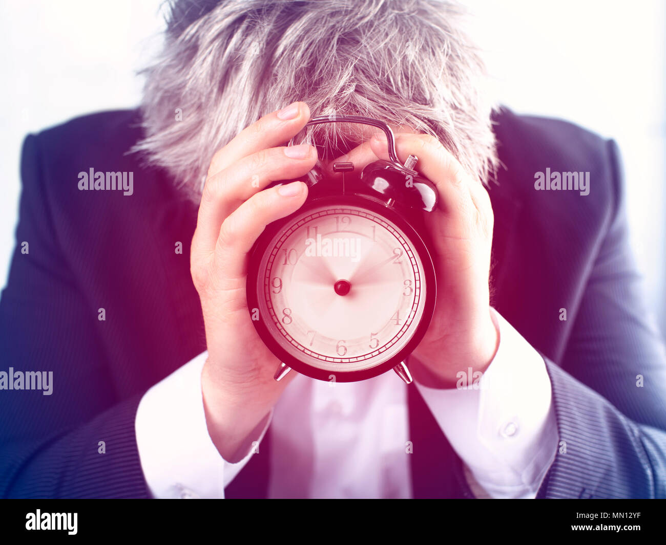 Man hiding face behind alarm clock on white background. Time management concept - Stock Image