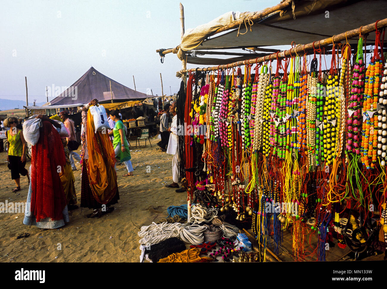 Pushkar, Rajasthan, India- May 23, 2008: Tourists at a necklaces, beads, jewelry, gemstones, bracelets, earrings, bangles, devotional objects at fair. - Stock Image