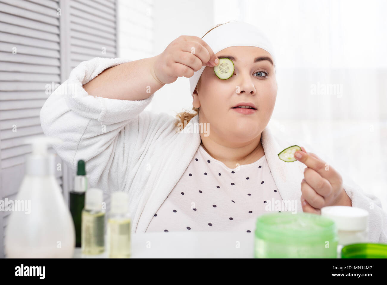 Serious fat woman making a cucumber mask - Stock Image