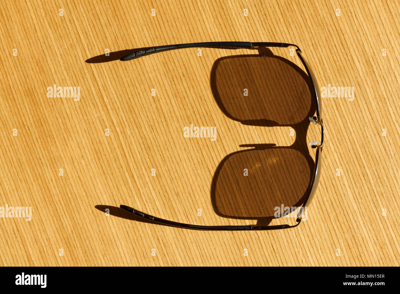 Sunglasses in sunshine on a wooden table - Stock Image
