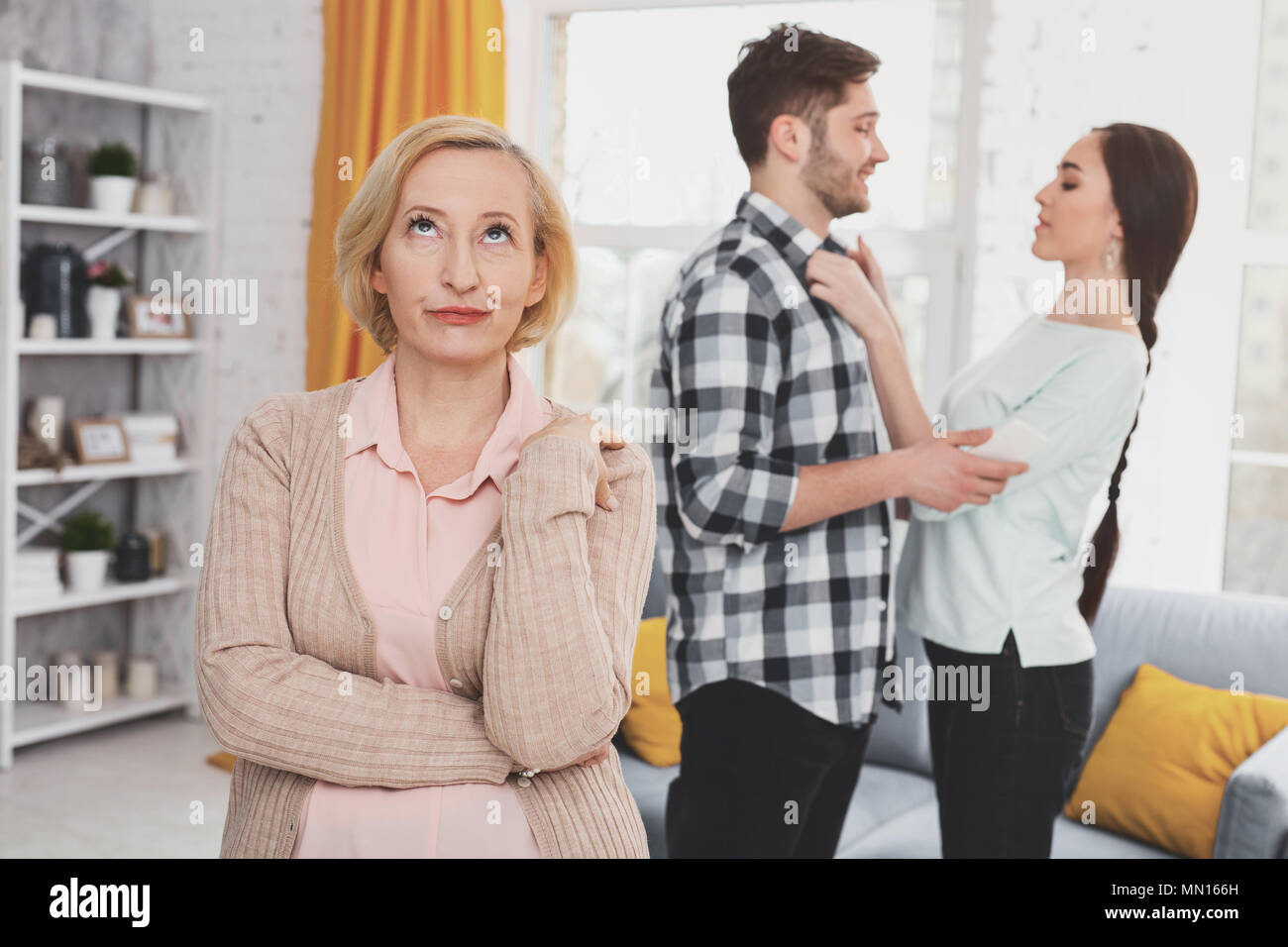 Unhappy aged woman standing in the living room - Stock Image