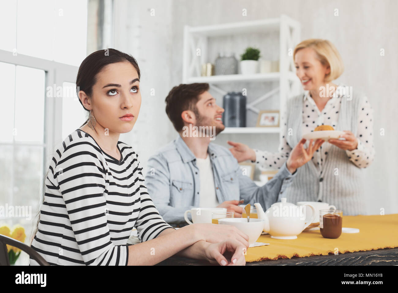 Cheerless young woman rolling her eyes - Stock Image