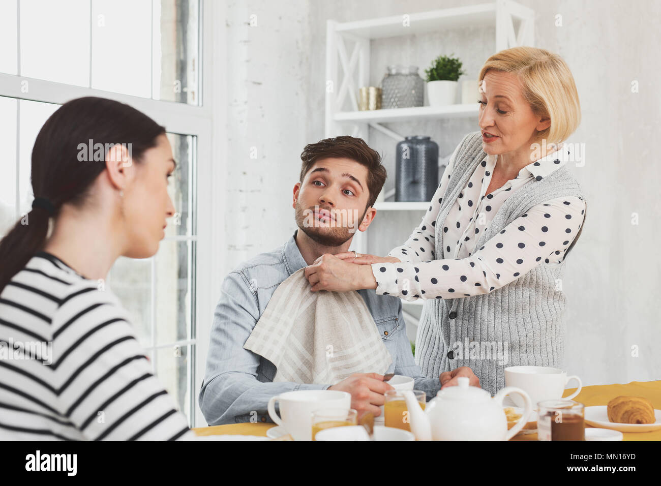 Pleasant aged woman caring about her son - Stock Image