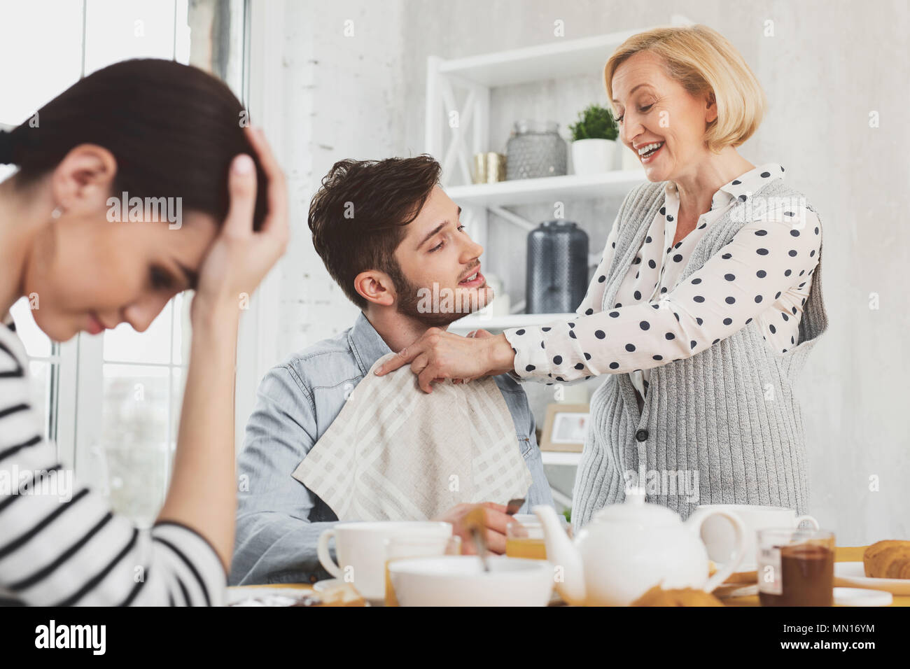 Cheerful positive woman smiling to her son - Stock Image