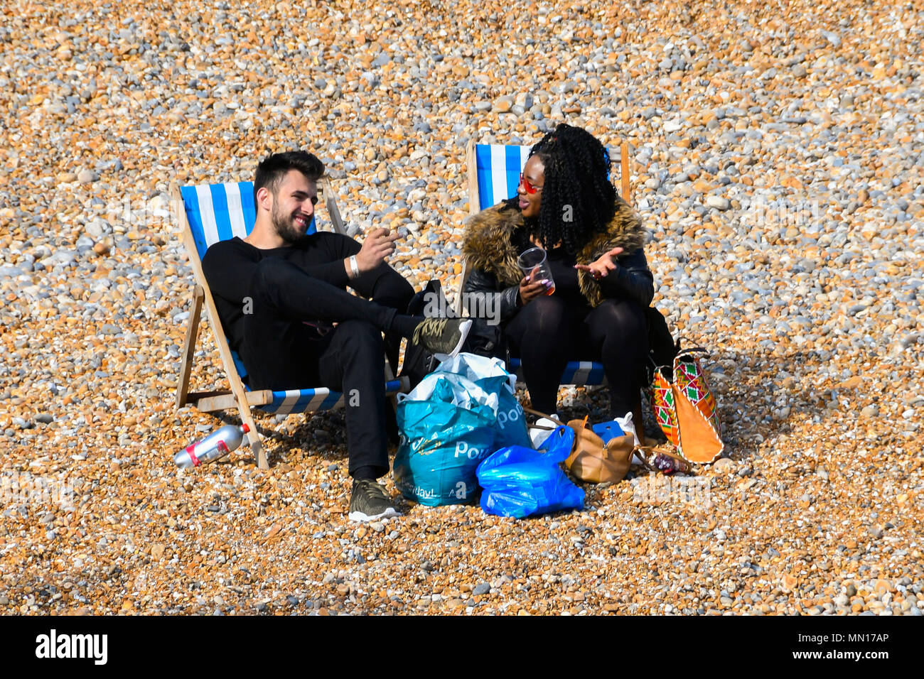 Brighton, West Sussex, UK.  13th May 2018. UK Weather.  Two people on the beach enjoying the warm afternoon sunshine at Brighton in West Sussex.  Picture Credit: Graham Hunt/Alamy Live News - Stock Image