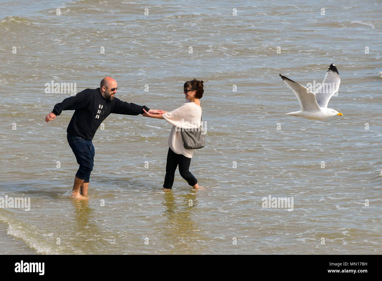 Brighton, West Sussex, UK.  13th May 2018. UK Weather.  A couple standing in the sea at the beach enjoying the warm afternoon sunshine at Brighton in West Sussex.  Picture Credit: Graham Hunt/Alamy Live News - Stock Image