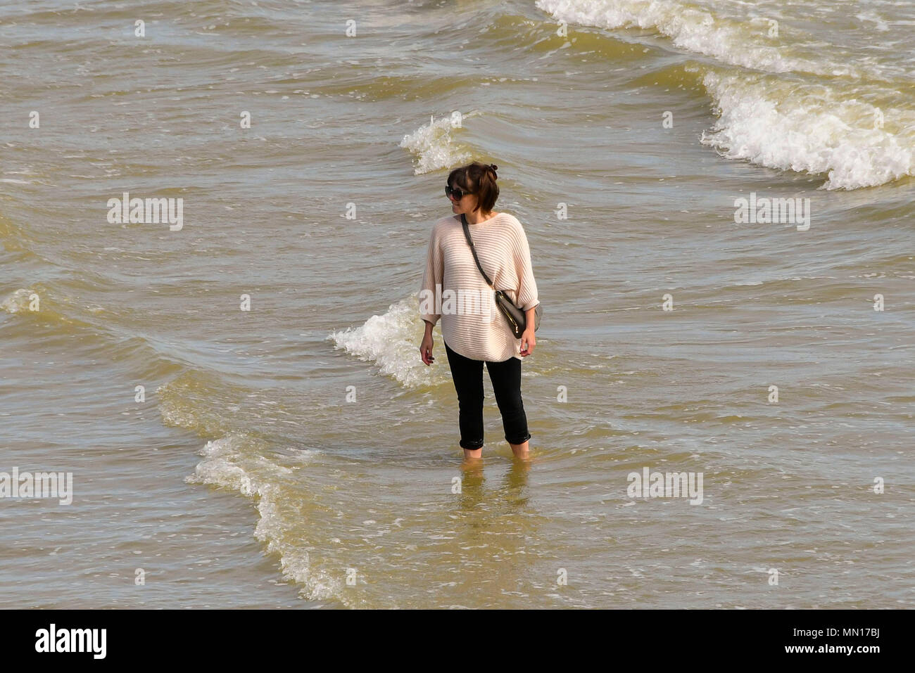 Brighton, West Sussex, UK.  13th May 2018. UK Weather.  A woman standing in the sea at the beach enjoying the warm afternoon sunshine at Brighton in West Sussex.  Picture Credit: Graham Hunt/Alamy Live News - Stock Image