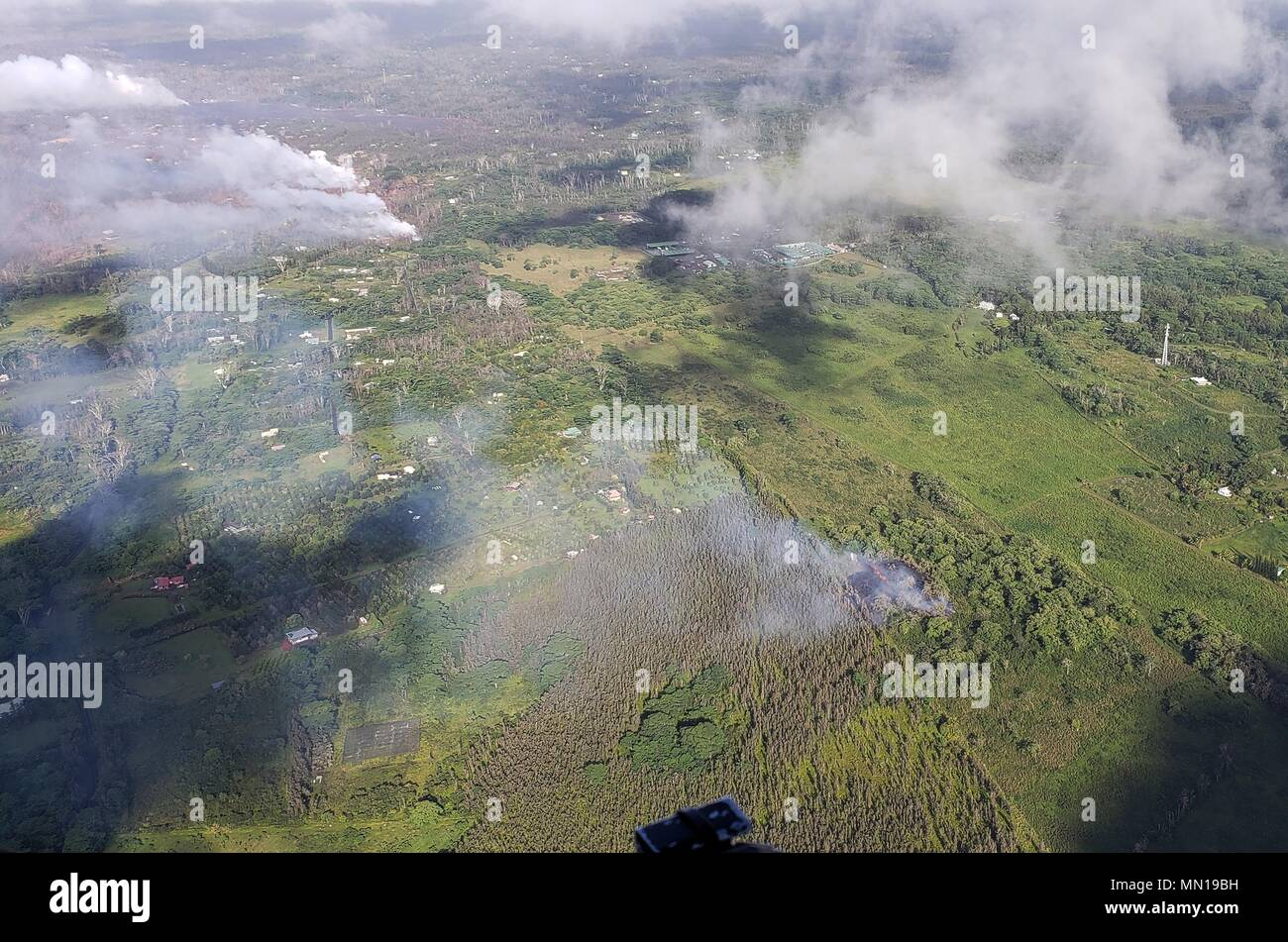 Hawaii, USA 12th May 2018. An aerial view of steam and lava escaping from newly formed fissure 16 from the Kilauea volcano May 12, 2018 in Leilani Estates, Hawaii. The fissure is located 500 meters northeast of the Puna Geothermal Venture site (top right). Credit: Planetpix/Alamy Live News Stock Photo