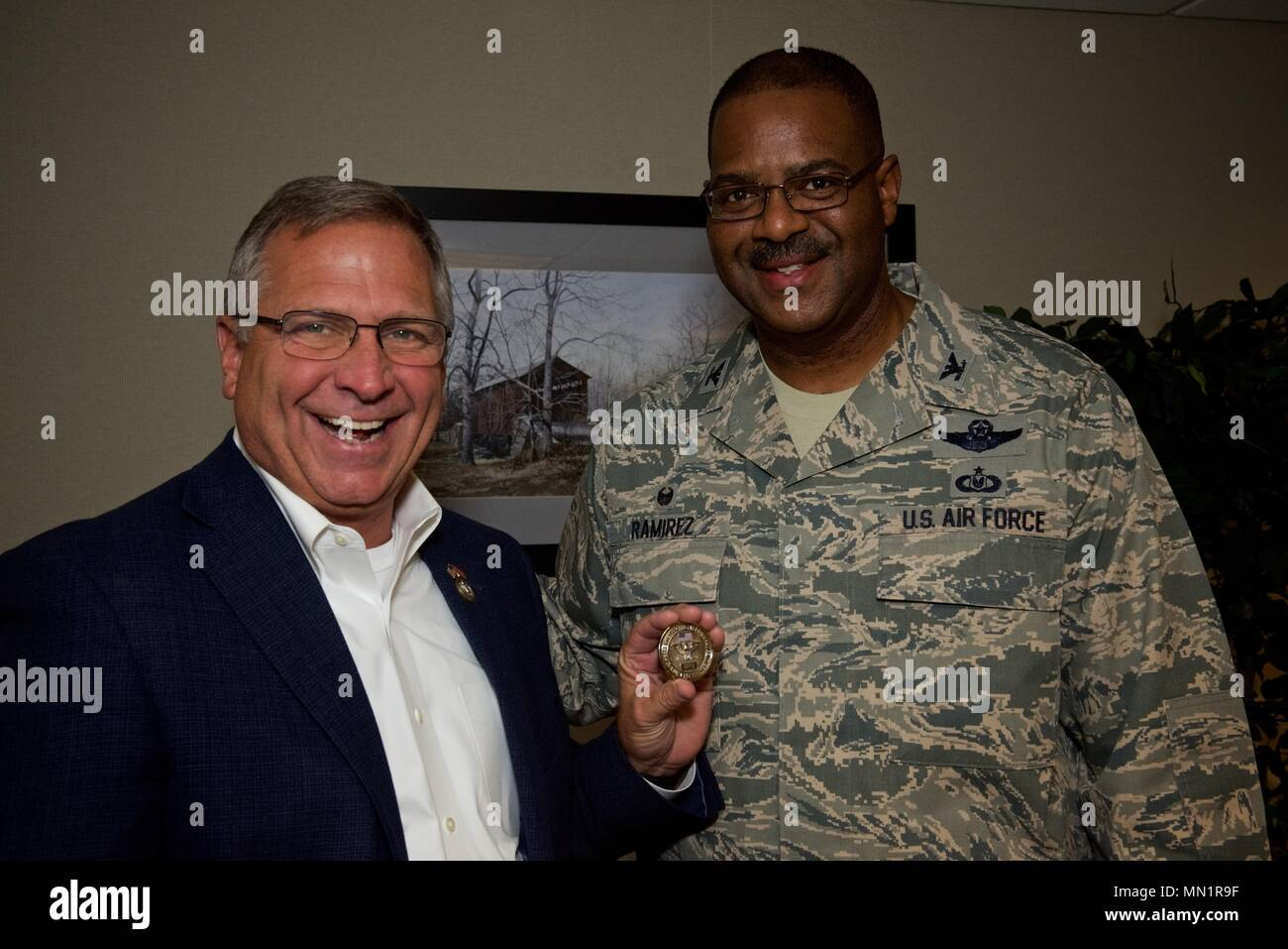 Congressman Mike Bost, representing the 12th district of Illinois, shows off the wing commanders's coin that Col. Esteban Ramirez, commander, 932nd Airlift Wing presented during Bost's visit Aug. 5, 2017, Scott Air Force Base, Illinois.   (U.S. Air Force photo by Tech. Sgt. Christopher Parr) - Stock Image