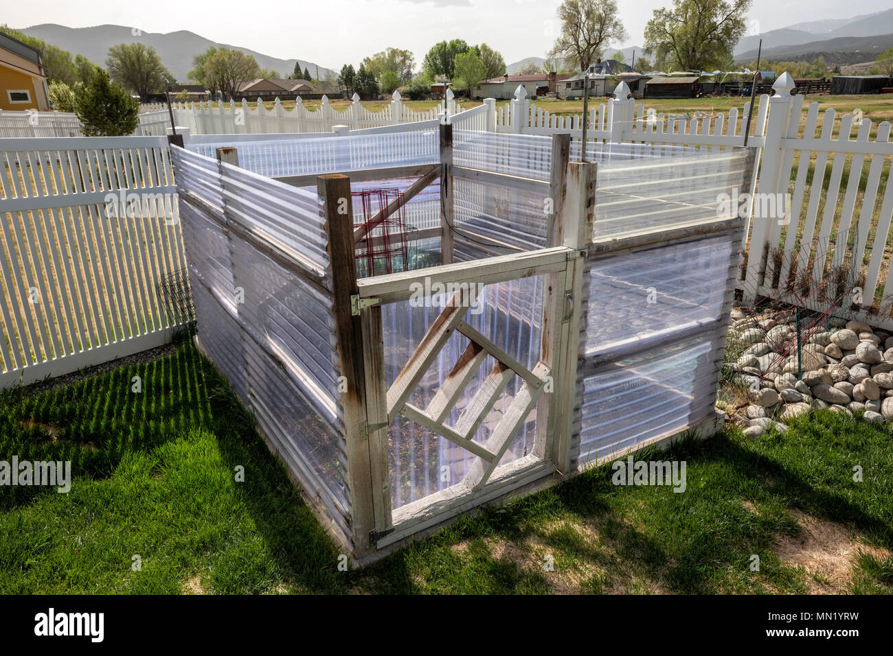 Residential vegetable garden with fiberglass panel walls to deflect wind Stock Photo
