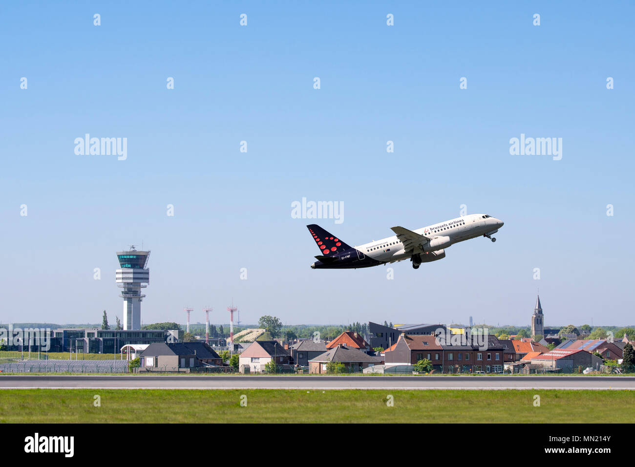 Control tower of Brussels Airport and the village Steenokkerzeel behind runway of Brussels Airlines while airplane is taking off, Zaventem, Belgium - Stock Image