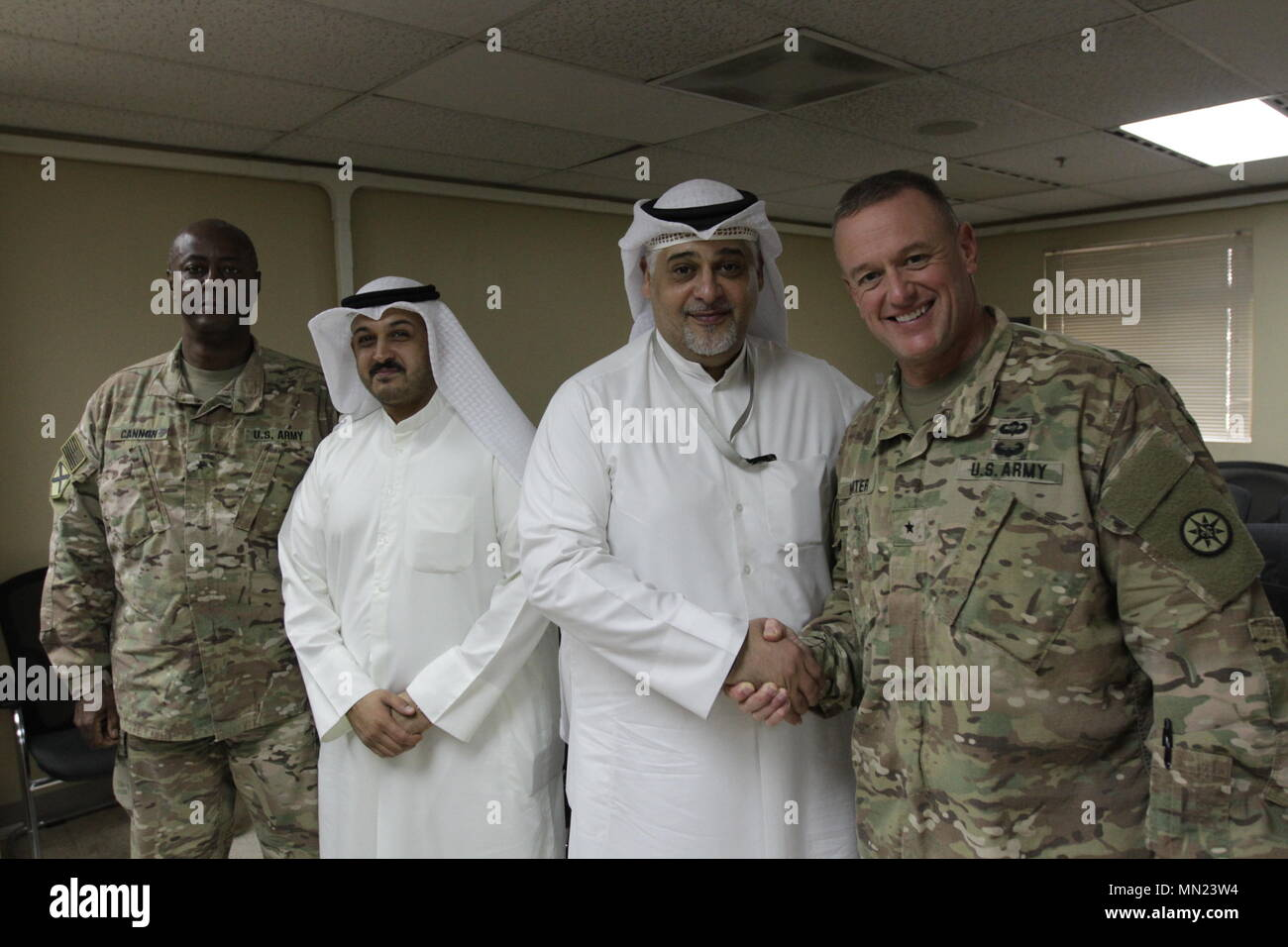 Brig. Gen. Robert D. Harter, Commanding General of the 316th Sustainment Command (Expeditionary), Deputy Commanding General of the 1st Sustainment Command (Theater), right, meets with Mr. Osama K. Al-Shami, Assistant Head of the Director and Deputy Office Head Kuwaiti Customs and US Military Liaison, left, during a meeting regarding maintenance and improvement of the facilities at Kubhari Crossing (K Crossing), a major Ground Logistical Operation Corridor between Kuwait and Iraq, on Aug. 14, 2017. (U.S. Army photo by Sgt. Christopher Bigelow) - Stock Image