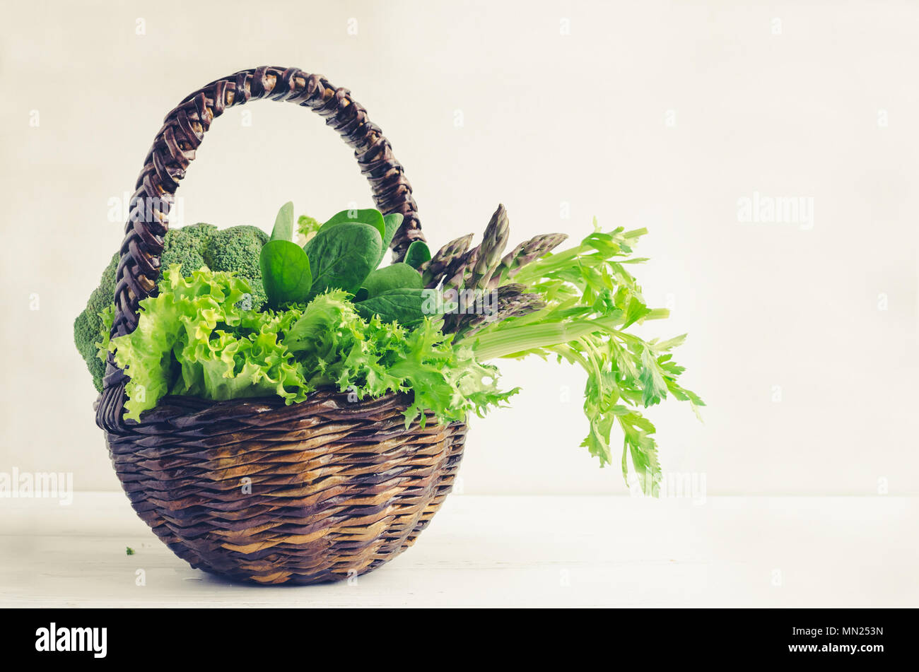 Assorted green vegetables in a basket on white wooden background with place for text. Fresh veggies and greens: spinach, fennel, celery, lettuce, aspa Stock Photo