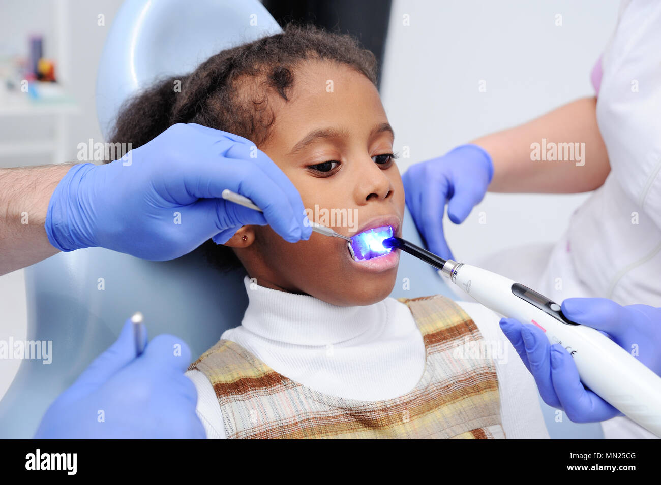 a dark-skinned baby girl in the dentist's chair - Stock Image
