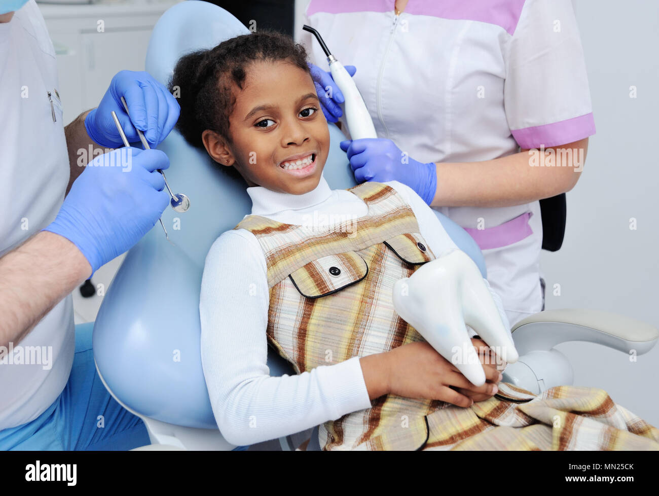 little African girl with dark skin in dentistry - Stock Image